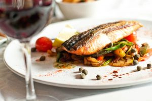 Closeup photograph of a plate with fish and vegetables with an unsharp glass of wine in the foreground. image by FlickreviewR